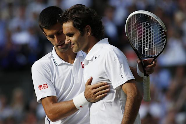 Novak Djokovic (L) speaks with Roger Federer after winning their men's singles final at The All England Tennis Club in Wimbledon, on July 6, 2014 (AFP Photo/Sang Tan)