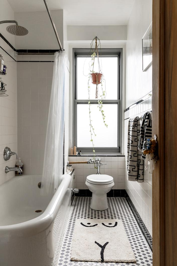 """<div class=""""caption""""> """"This is a hundred-year-old bathroom,"""" Molly says. """"I put in a <a href=""""https://www.architecturaldigest.com/story/what-to-look-for-in-a-shower-head?mbid=synd_yahoo_rss"""" rel=""""nofollow noopener"""" target=""""_blank"""" data-ylk=""""slk:shower head"""" class=""""link rapid-noclick-resp"""">shower head</a> and bath handle, but other than that, I was charmed by its original details. Some of the tiles are old and broken, but I didn't buy in a new development for a reason—I wanted some history here."""" </div>"""