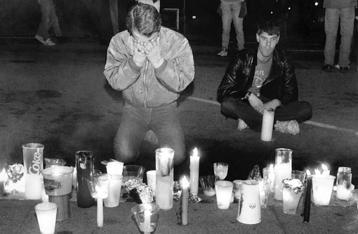 In this May 21, 1990 file picture, Scotty McQuown of San Francisco, left, weeps in front of a makeshift memorial to AIDS victims during the seventh annual International AIDS Candlelight Memorial in San Francisco. Up to 20,000 people gathered in front of San Francisco's City Halll to remember those lost to the disease and those still fighting it.