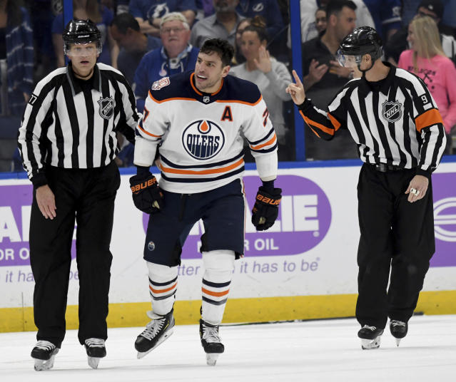Linesman Tim Nowak (77) skates Edmonton Oilers left wing Milan Lucic (27) toward the penalty box during the third period of the team's NHL hockey game against the Tampa Bay Lightning on Tuesday, Nov. 6, 2018, in Tampa, Fla. (AP Photo/Jason Behnken)