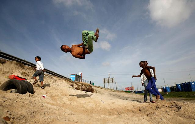 <p>Youths somersault over old tires in the Khayelitsha township, near Cape Town, South Africa May 25, 2017. (Photo: Mike Hutchings/Reuters) </p>