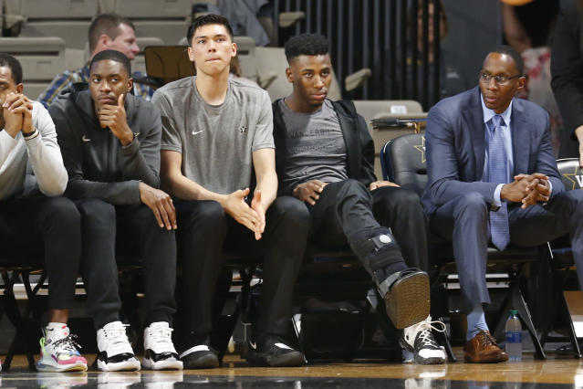 Injured Vanderbilt sophomore guard Aaron Nesmith, second from right, wears a walking boot as he watches his teammates play Texas A&M in an NCAA college basketball game Saturday, Jan. 11, 2020, in Nashville, Tenn. Nesmith is the SEC's leading scorer and fifth nationally averaging 23 points a game. Texas A&M won 69-50. (AP Photo/Mark Humphrey)