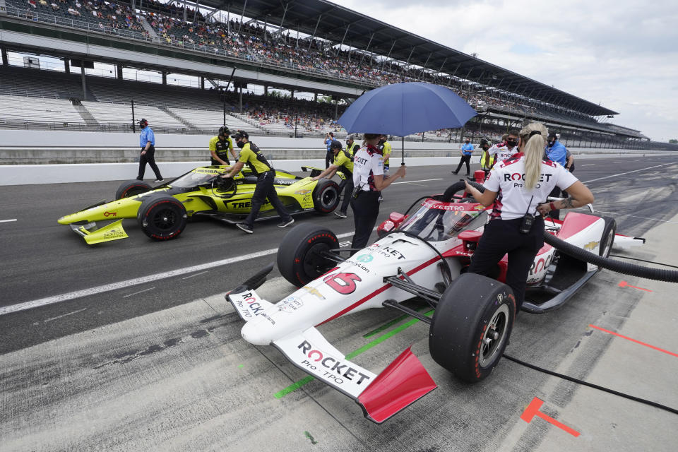 Simona De Silvestro, foreground, of Switzerland, sits in her car as the crew of Charlie Kimball pushes his car to the qualification line during qualifications for the Indianapolis 500 auto race at Indianapolis Motor Speedway, Sunday, May 23, 2021, in Indianapolis. (AP Photo/Darron Cummings)
