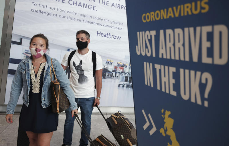 Passengers Charlotte and Frank, arrive at Heathrow Airport as they return from Mykonos in Greece, after the British Government added the island to the coronavirus quarantine list, at Heathrow, London, Tuesday Sept. 8, 2020. From early Wednesday, people arriving from several Greek islands will need to self-isolate for 14-days, but mainland Greece will maintain its quarantine-exemption, according to Britain's Transport Secretary Grant Shapps, who said that England is to start applying a regional approach to its coronavirus quarantine policy. (Yui Mok/PA via AP)