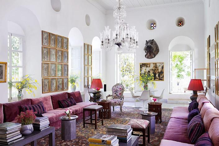 """<p>The many facets of a crystal chandelier will reflect other light sources, including the sun and lamps, throughout a space. In this <a href=""""https://www.elledecor.com/design-decorate/house-interiors/a31152964/beit-trad-lebanon/"""" rel=""""nofollow noopener"""" target=""""_blank"""" data-ylk=""""slk:Lebanese mountain home"""" class=""""link rapid-noclick-resp"""">Lebanese mountain home</a>, a Turkish chandelier is centered in a room with oversize windows.</p>"""