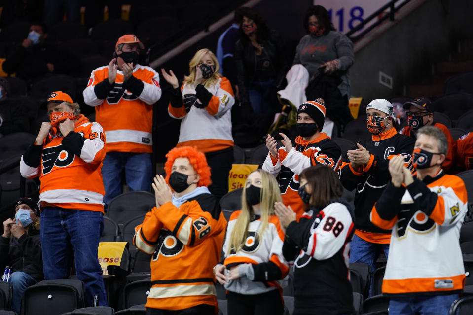 Fans cheer during the second period of an NHL hockey game between the Philadelphia Flyers and the Washington Capitals, Sunday, March 7, 2021, in Philadelphia. (AP Photo/Matt Slocum)
