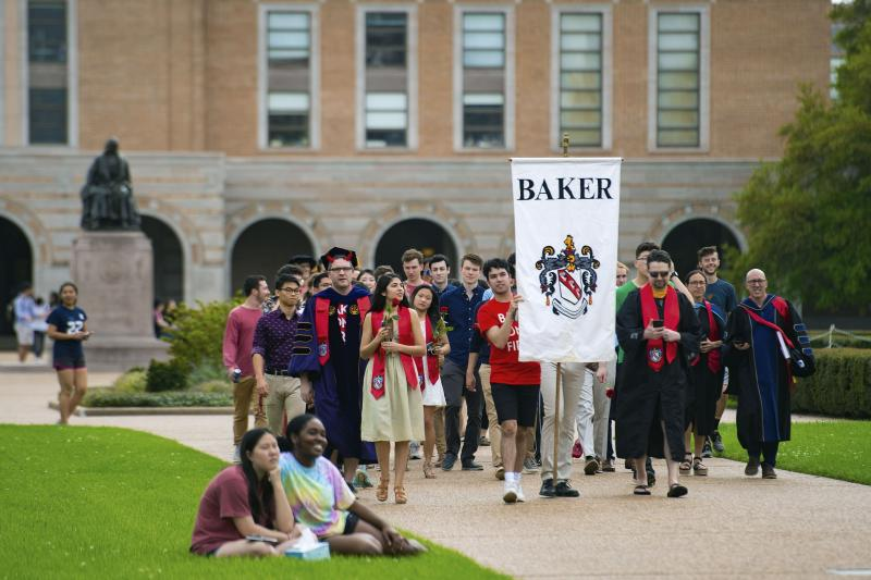 In this March 13, 2020 photo, seniors at Rice University parade toward the school's main archway, known as the Sallyport, to continue a commencement tradition at the school in Houston. Due to the coronavirus outbreak it's not clear whether the campus will reopen in time for graduation. The new coronavirus causes mild or moderate symptoms for most people, but for some, especially older adults and people with existing health problems, it can cause more severe illness or death. (Jeff Fitlow/Rice University via AP)