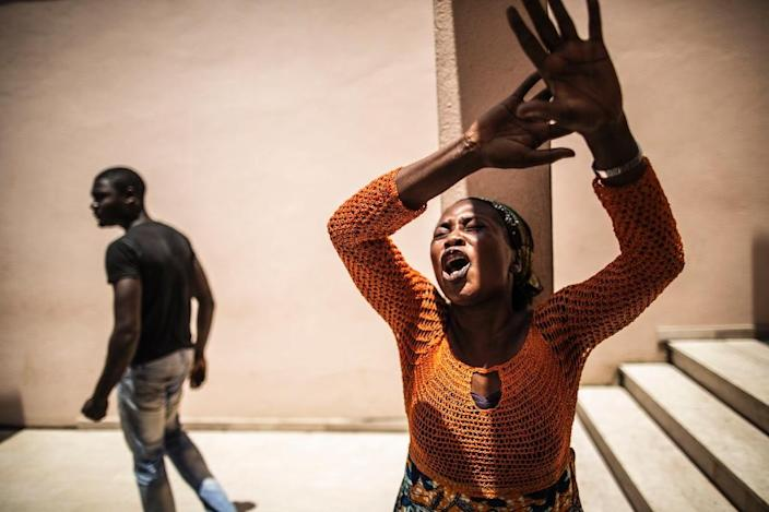 A distressed Gabonese woman reacts at the Libreville Magistrate Court on September 6, 2016, while she waits to hear about the release of young men arrested during a wave of unrest that followed the results of the election (AFP Photo/Marco Longari)
