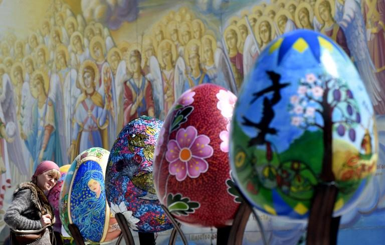 <p>Ukraine: A woman looks at huge Easter eggs as they walk in the open air festival in the center of Kiev on April 12, 2017.<br />Some 500 traditional Ukrainian pysankas, painted Easter eggs, are presented in the center of Kiev before the celebration of the Easter, main holiday of the Orthodox church, on April 16. / AFP PHOTO / Sergei SUPINSKY </p>