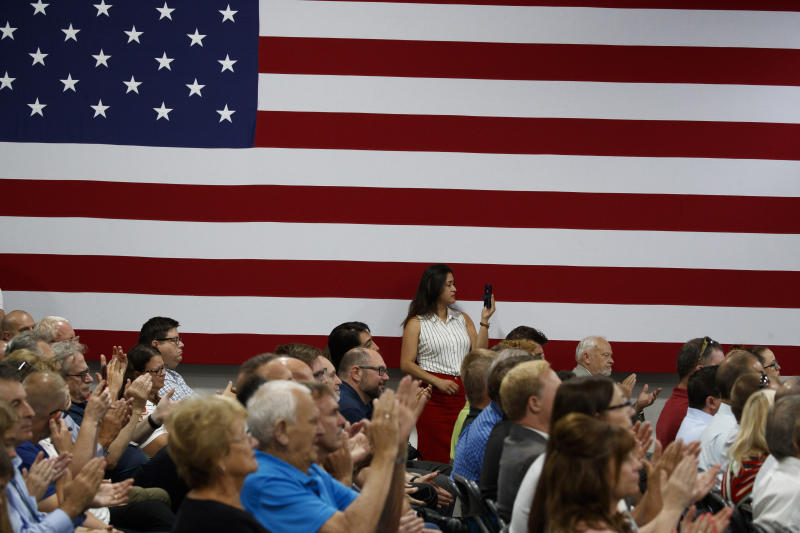 A member of the audience photographs President Donald Trump as he speaks at Derco Aerospace Inc., a subsidiary of Lockheed Martin, Friday, July 12, 2019, in Milwaukee. (AP Photo/Alex Brandon)