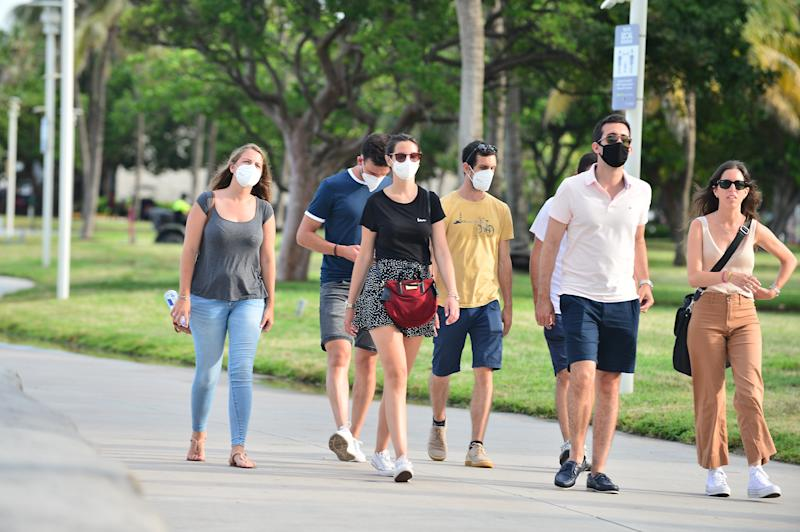 MIAMI BEACH, FL - JULY 06: People seen walking on the beach side walk some wearing mask and some not wearing a face mask on July 06, 2020 in Miami Beach, Florida. Miami Beach has mandated that masks be worn in public, where social distancing is not possible. With a surge in COVID-19 cases, Mayor Carlos Gimenez on Monday has ordered the closing of all restaurants, gyms and fitness centers, ballrooms and short-term vacation rentals. Mayor Gimenez will allow beaches to re-open on July 7th after being closed over the 4th of July weekend. (Photo by Johnny Louis/Getty Images)