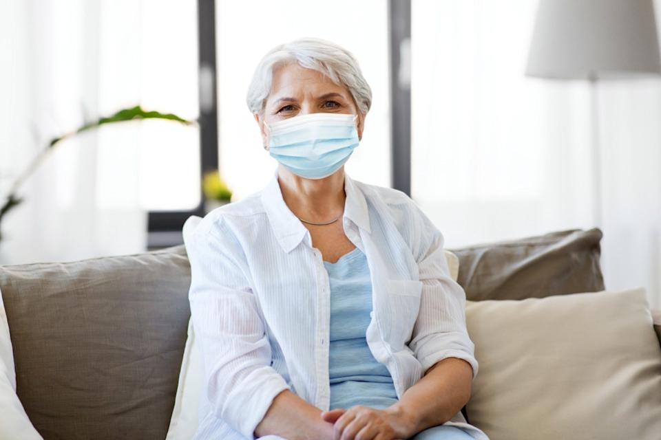 senior woman wearing protective medical mask for protection from virus at home
