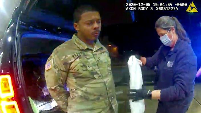 In this image made from Windsor Police video, Caron Nazario is helped by an EMT after he was sprayed with an agent by Windsor police after a traffic stop on Dec. 20, 2020, in Windsor, Va.  Nazario, a second lieutenant in the U.S. Army, is suing two Virginia police officers over a traffic stop during which he says the officers drew their guns and pointed them at him as he was dressed in uniform. Caron Nazario says his constitutional rights were violated by the traffic stop in the town of Windsor in December.
