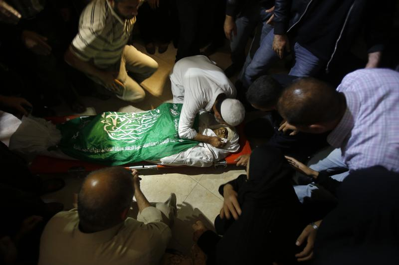 A Palestinian relative of Hamas militant Rabee Baraka kisses his body during his funeral at his family's house in Khan Younis in the southern Gaza Strip