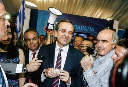 New Democracy party leader Antonis Samaras (C) smiles at supporters after his party came first in the national Greek's election, in central Athens. Greece's two main pro-bailout parties clinched enough votes to form a government in knife-edge elections on Sunday, as world powers pushed for a new cabinet as soon as possible to ease global fears