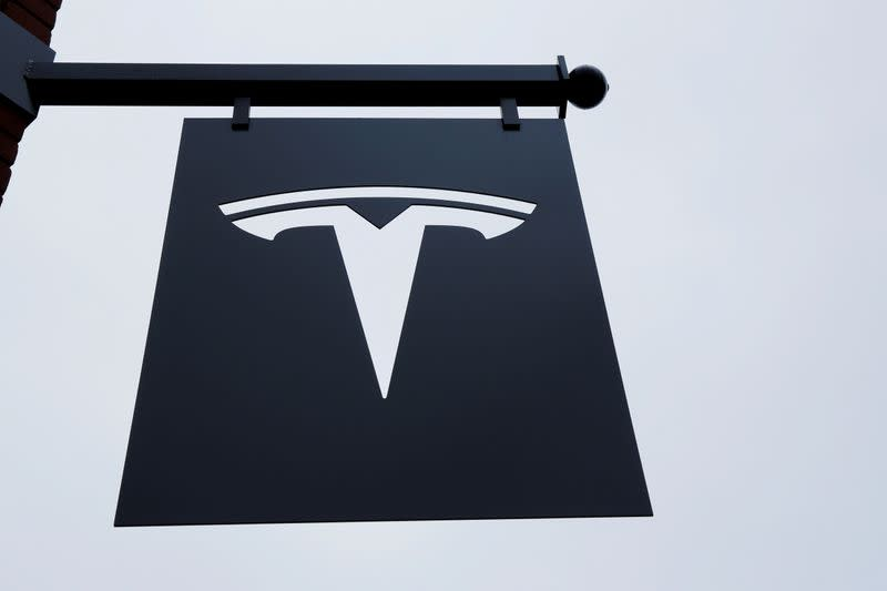 A Tesla logo hang on a building outside of a Tesla dealership in New York