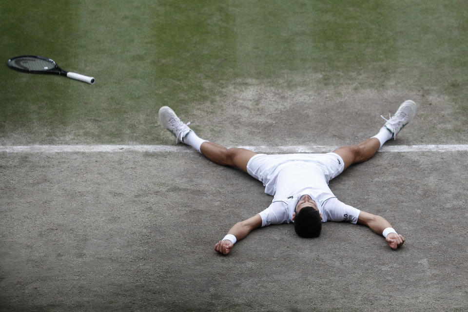 Serbia's Novak Djokovic collapses as he celebrates after defeating Italy's Matteo Berrettini in the men's singles final on day thirteen of the Wimbledon Tennis Championships in London, Sunday, July 11, 2021. (Pete Nichols/Pool Via AP)