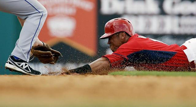 St. Louis Cardinals' Kolten Wong, right, slides into the tag of New York Mets' Daniel Murphy as he's caught stealing second base in the fourth inning of an exhibition spring training baseball game, Sunday, March 16, 2014, in Jupiter, Fla. (AP Photo/David Goldman)