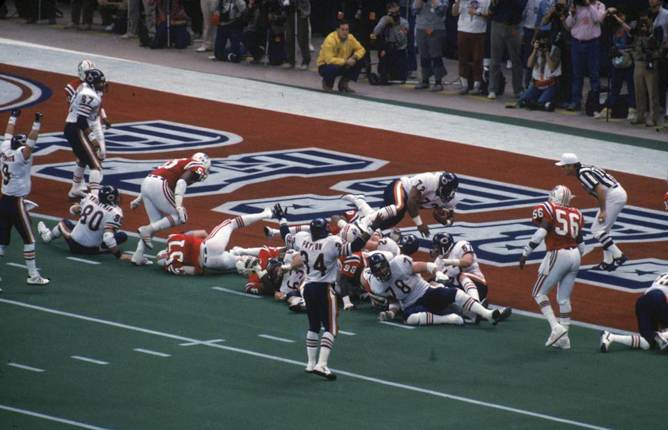 """NEW ORLEANS, LA - JANUARY 26:  Defensive tackle William """"The Refrigerator"""" Perry #72 of the Chicago Bears scores a touchdown against the New England Patriots in Super Bowl XX at the Superdome on January 26,1986 in New Orleans, Louisiana. The Bears defeated the Patriots 46-10. (Photo by Gin Ellis/Getty Images)"""
