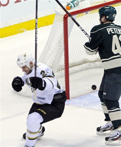 Dallas Stars' Eric Nystrom, left, celebrates his goal off Minnesota Wild goalie Josh Harding in the first period of an NHL hockey game, Saturday, Jan. 21, 2012, in St. Paul, Minn. At right is Wild's Warren Peters. (AP Photo/ Jim Mone)