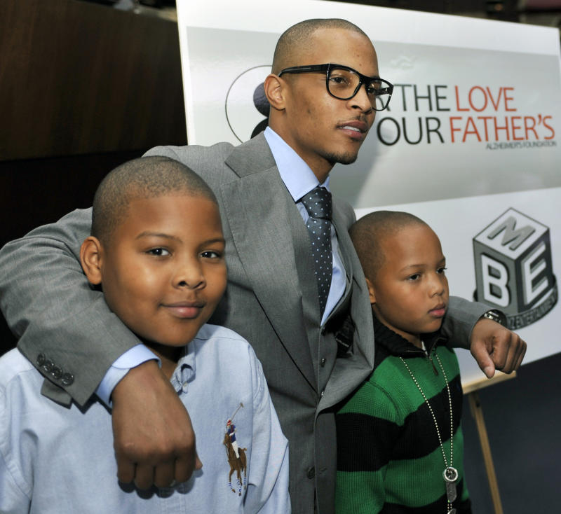 """Grammy award winning artist Clifford """"TI"""" Harris, center, poses for photographers with his sons Messiah, left, 10, and Domani, right, 9, during an Alzheimers """"For the Love of Our Fathers"""" foundation honoree luncheon at the Luckie Lounge Sunday, Oct.  3, 2010, in Atlanta. (AP Photo/Gregory Smith)"""