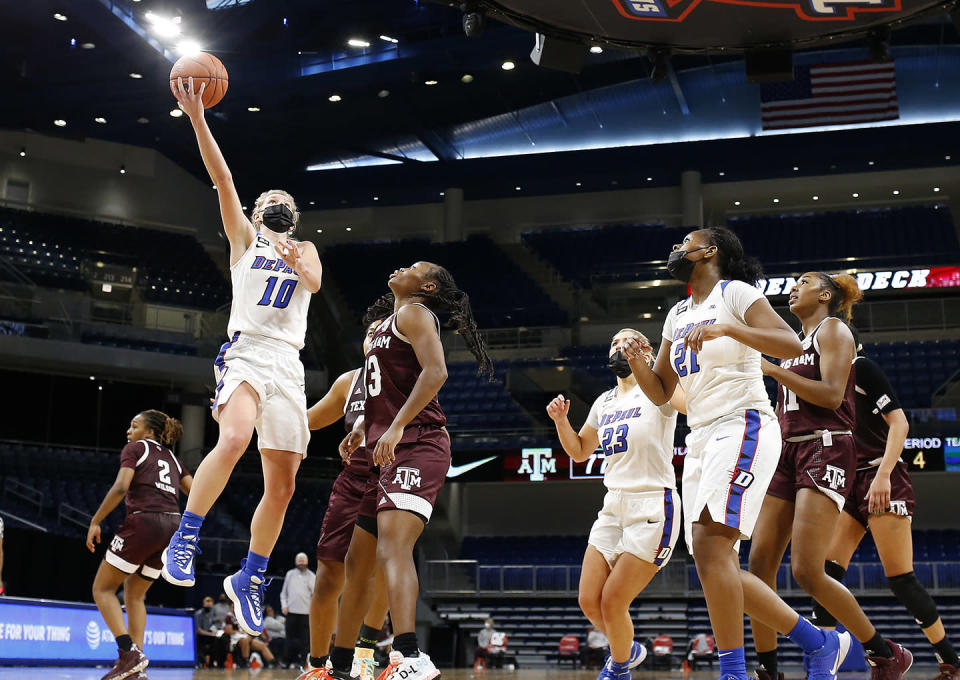 In this photo provided by DePaul Athletics, DePaul's Lexi Held (10) goes to the basket against Texas A&M as teammates Dee Bekelja (23) and Darrione Rogers (21) look on during an NCAA college basketball game on Saturday, Nov. 28, 2020, in Chicago. It's a common sight to see players and coaches wear masks on the sideline so far this season during college basketball games to help prevent the spread of the coronavirus. The DePaul and Creighton women's basketball teams are among a few squads that have taken it a step further with their players wearing the masks while they are on the court playing. (Steve Woltman/DePaul Athletics via AP)