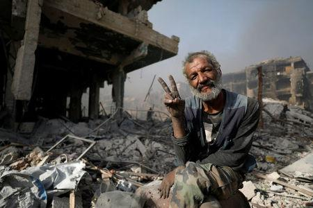 A man gestures as he sits on the rubble of damaged buildings in al-Hajar al-Aswad, Syria May 21, 2018. REUTERS/Omar Sanadiki
