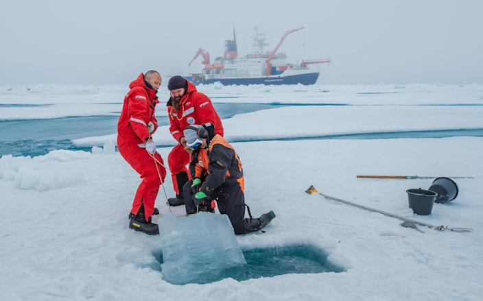 Scientists haul a sample of ice from the Arctic Ocean as part of research into the effects of climate change on the sensitive region as their vessel, the RV Polarstern, waits behind them. / Credit: Alfred Wegener Insititute / Lianna Evans Nixon