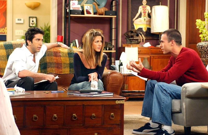 Ross (David Schimmer) and Rachel (Jennifer Aniston) sit with a piece of furniture that's become famous: The Pottery Barn Apothecary Table.