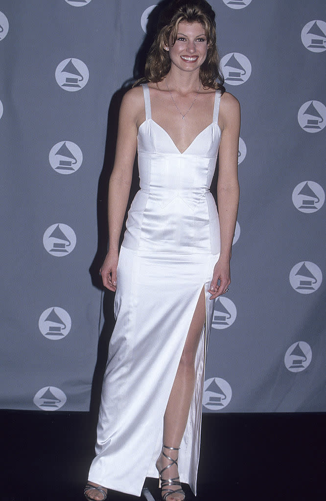 <p>This country songstress looked angelic when she showed up to the 1995 Grammy Awards in this sleek, white, bodycon gown — likely breaking hearts all over the world. (Image via Getty Images)</p>
