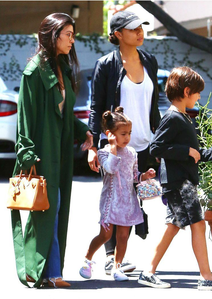 North West toting a Fendi clutch to church