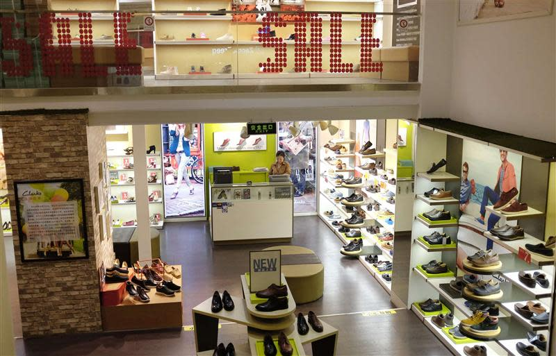 A saleswoman waits for customers at a shoe store in a shopping mall in Beijing