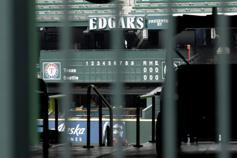The manual scoreboard at T-Mobile Park in Seattle is seen through the bars of an entry gate, Thursday, March 26, 2020, on the day that would have been the Mariners' Opening Day baseball game against the visiting Texas Rangers. Earlier in the month, Major League Baseball called off the start of the season due to the outbreak of the new coronavirus. (AP Photo/Ted S. Warren)