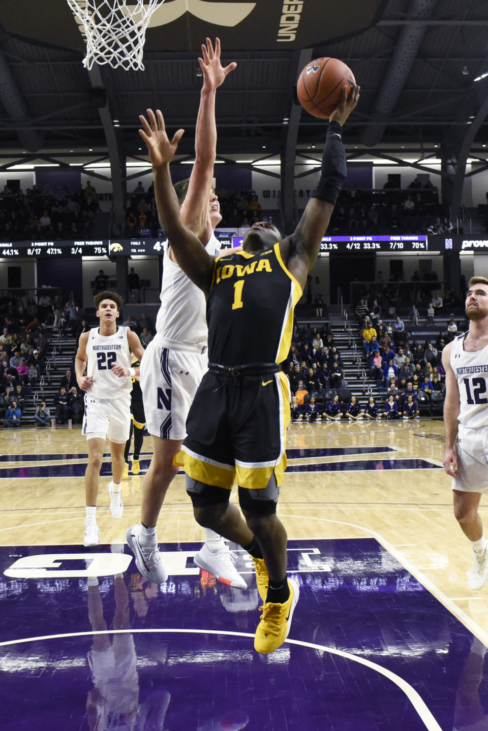Iowa guard Joe Toussaint (1) goes to the basket as Northwestern center Ryan Young (15) defends during the second half of an NCAA college basketball game Tuesday, Jan. 14, 2020, in Evanston, Ill. (AP Photo/David Banks)