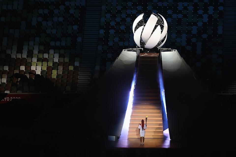 <p>TOKYO, JAPAN - JULY 23: Naomi Osaka of Team Japan carries the Olympic torch towards the Olympic cauldron during the Opening Ceremony of the Tokyo 2020 Olympic Games at Olympic Stadium on July 23, 2021 in Tokyo, Japan. (Photo by Laurence Griffiths/Getty Images)</p>
