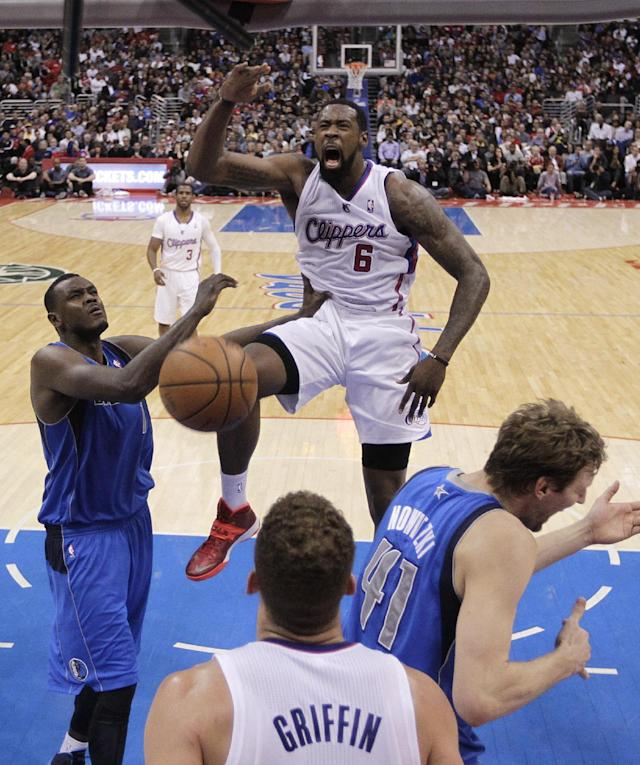 Los Angeles Clippers' DeAndre Jordan (6) dunks in front of Dallas Mavericks' Samuel Dalembert (1) and Dirk Nowitzki (41) during the first half of an NBA basketball game Thursday, April 3, 2014, in Los Angeles. (AP Photo/Jae C. Hong)