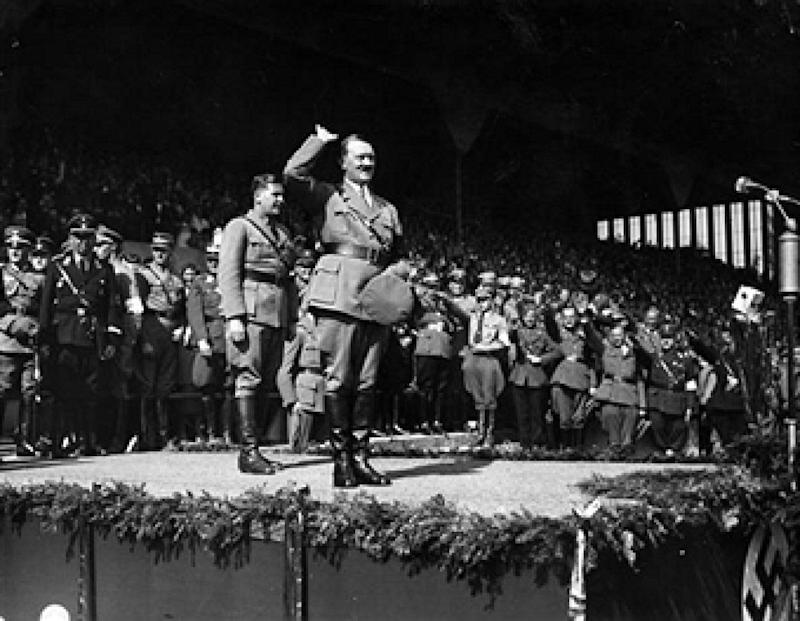 19th December 1934: German chancellor Adolf Hitler salutes a crowd of 60,000 at a Hitler Youth rally at Nuremberg. (Photo by Central Press/Getty Images)