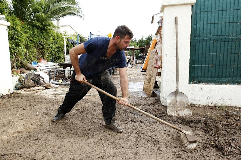 A man cleans up his house in Biot, a day after floods tore through southeastern France, on October 5, 2015 (AFP Photo/Jean-Christophe Magnenet)