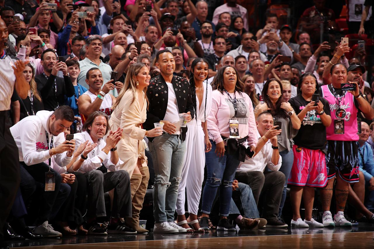John Legend, Chrissy Teigen, and Gabrielle Union seen courtside during the game between the Philadelphia 76ers and the Miami Heat on April 9, 2019 at American Airlines Arena in Miami, Florida. Photo courtesy of Getty Images.