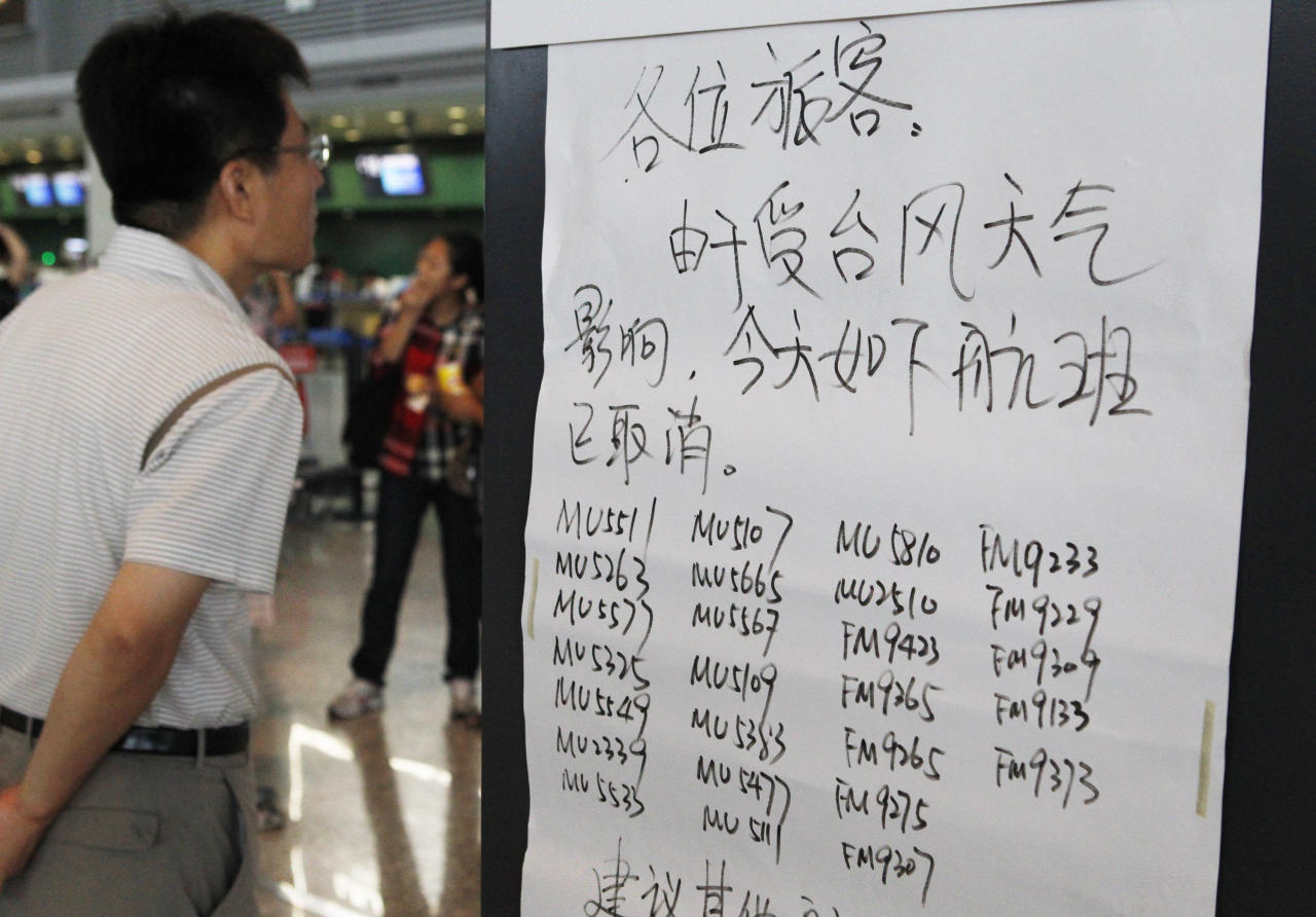 A man stands near an airline notice of the list of the canceled flights due to Typhoon Muifa at Honqiao Airport in Shanghai, China, Sunday, Aug. 7, 2011. Typhoon Muifa is forecast to hit China early Monday morning, making landfall in the eastern province of Shandong and skimming the coast as it heads north, China's Central Meteorological Administration said. (AP Photo/Eugene Hoshiko)
