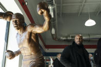 Joe Frazier Jr., looks at a statue of his father Joe Frazier, left, fighting Muhammad Ali, on the 50th anniversary of the boxers' World Heavyweight Championship boxing bout, at the Joe Hand Gym in Feasterville, Pa., Monday, March 8, 2021. (AP Photo/Matt Rourke)