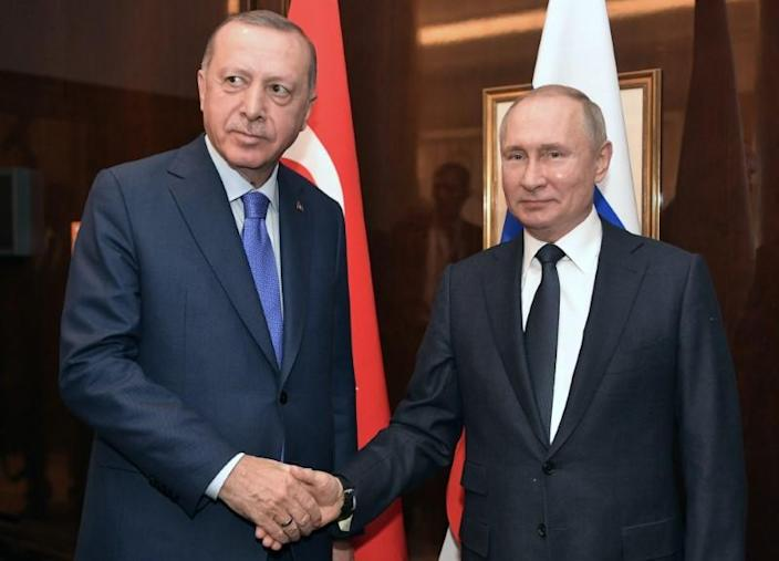 Russian President Vladimir Putin and his Turkish counterpart Tayyip Erdogan shakes hands during their meeting on sideline of the Libya summit in Berlin