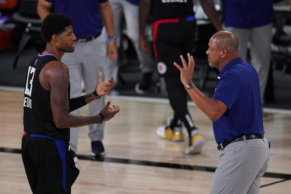 Los Angeles Clippers head coach Doc Rivers, right, talks with Paul George (13) during the second half of an NBA conference semifinal playoff basketball game against the Denver Nuggets Saturday, Sept. 5, 2020, in Lake Buena Vista, Fla. (AP Photo/Mark J. Terrill)