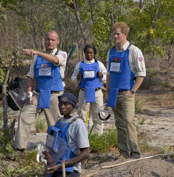 In this handout photo made available by the HALO Trust on Saturday, Aug. 17, 2013, Gerhard Zank, left, deminer Mateus Canhanga, foreground, section leader Maria Ilda da Piedade, center, and Britain's Prince Harry, discuss clearance techniques. Harry returned from Angola, where he visited a landmine clearance charity championed by his late mother, Princess Diana. The HALO Trust charity said Saturday the 28-year-old prince visited the Angolan town of Cuito Cuanavale, which saw heavy fighting during the southern African nation's 1975-2002 civil war. The group said Harry toured minefields and met beneficiaries of the group's work. (AP Photo/HALO Trust)