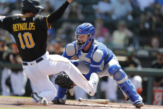 Toronto Blue Jays catcher Reese McGuire waits on the throw as Pittsburgh Pirates' Bryan Reynolds begins his slide during a spring training baseball game, Thursday, March 12, 2020, in Bradenton, Fla. (AP Photo/Carlos Osorio)