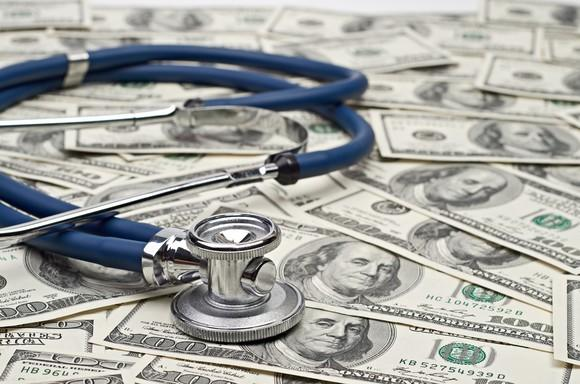 A blue stethoscope atop hundred dollar bills.
