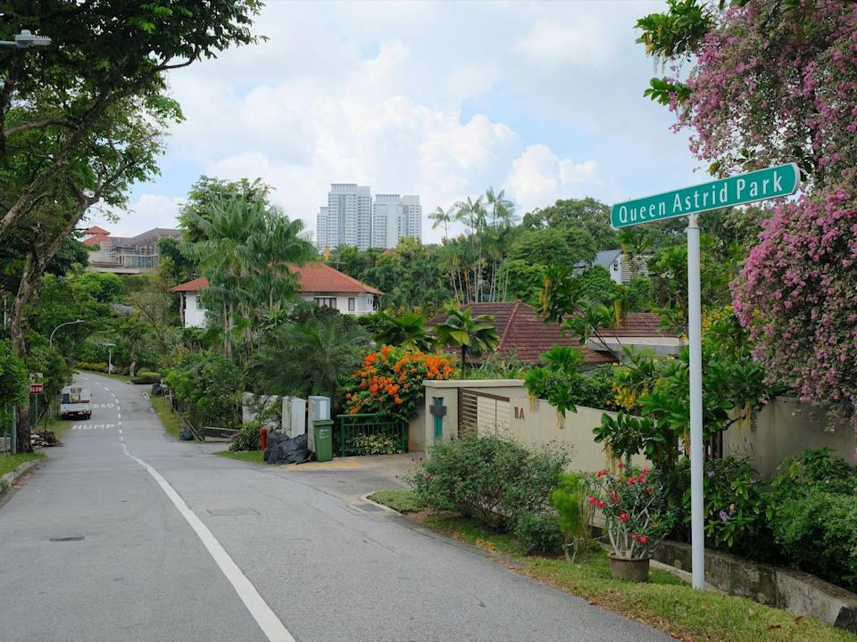 a view of houses and trees at queen astrid park, an upscale street in singapore
