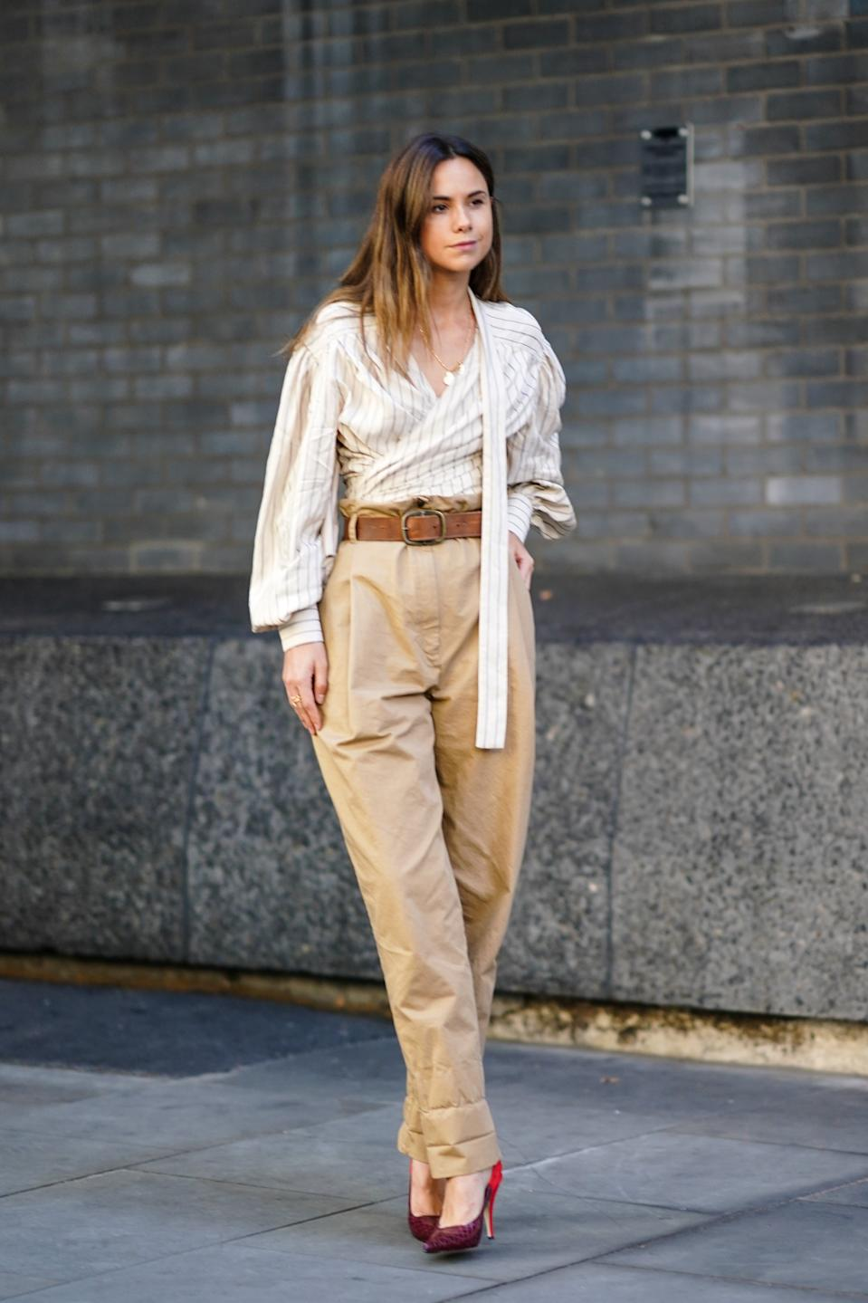 A guest is seen wearing high waisted brown trousers and a striped shirt. [Photo: Getty Images]