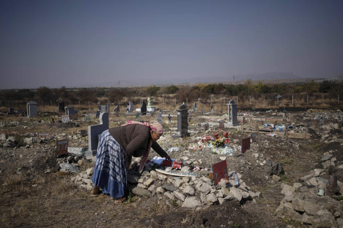 Rebecca Mohapi, who's son Onthatile died last year, puts one of his favorite toys on his grave in Damonsville, South Africa, on June 8, 2020. She believes her son's death wasn't an accident and that he was murdered. (AP Photo/Bram Janssen)
