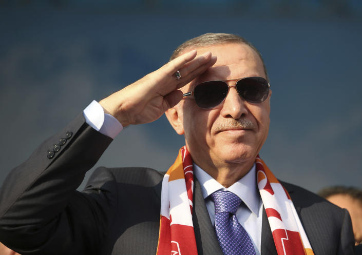 Turkish President Recep Tayyip Erdogan gives a military style salute toward his supporters during a rally in Kayseri, Turkey, Saturday, Oct. 19, 2019. Turkish Red Crescent says it has delivered humanitarian aid for 2000 people in Syrian town of Ras Al-Ayn and says it also provided aid to Tal Abyad and will continue to do so in areas cleared from Syrian Kurdish fighters.(Presidential Press Service via AP, Pool )
